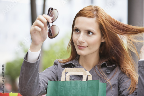 Young woman looking at sunglasses