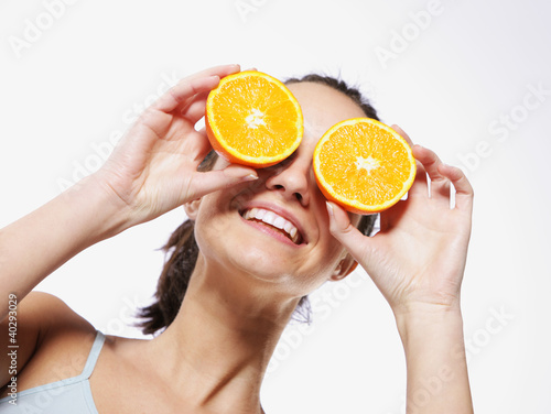 Funny girl portrait, holding oranges over eyes, diet concept