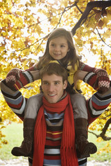 Father carrying daughter on shoulders, smiling