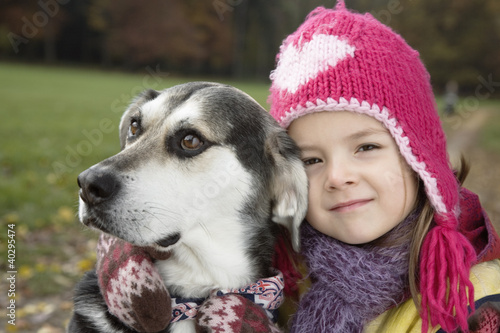 Girl hugging with dog in garden, portrait