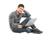 A smiling male with a laptop looking at camera