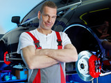 Motor mechanic in a garage next to a car on a service lift