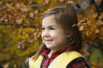 Girl smiling in garden, side view
