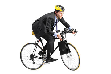 A young businessman riding a bicycle going towards his workplace