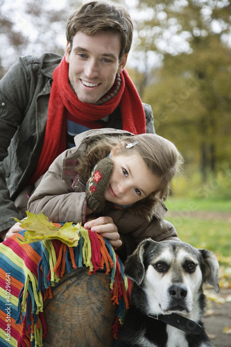 Father and daughter smiling with dog