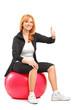 Portrait of a smiling mature female sitting on a pilates ball an