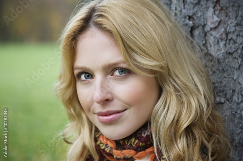 Young woman leaning by tree trunk, portrait, close-up