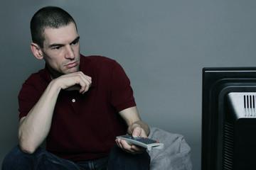 homme regardant la télévision en zappant