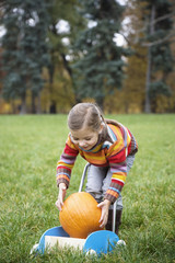 Girl holding pumpkin in cart, smiling