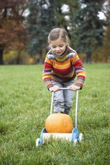 Girl pushing cart of pumpkin, smiling