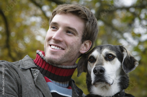Young man with dog, smiling