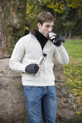 Young man drinking tea with thermos cup