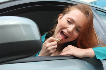 Pretty redhead woman put on make-up at her car