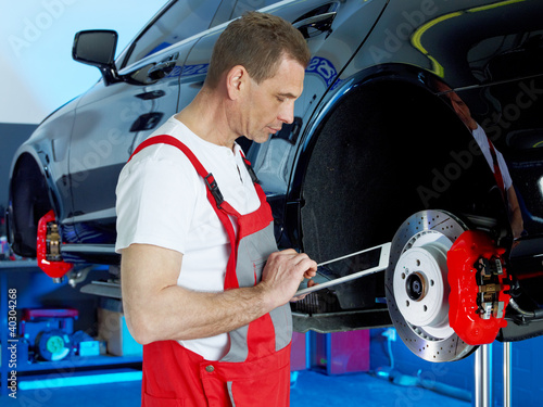 Master mechanic inspecting a break of a car with touchpad