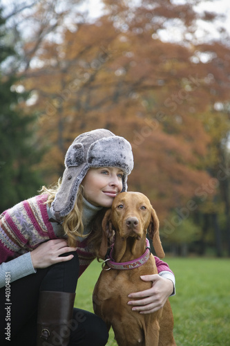 Young woman smiling with dog in garden, looking away