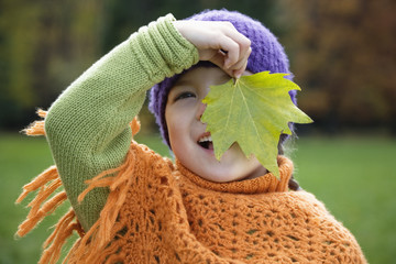 Girl holding maple leaf, smiling, portrait
