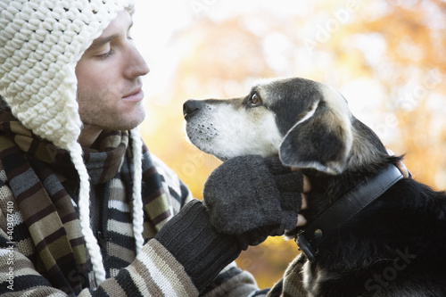 Young man looking at dog, side view, close-up