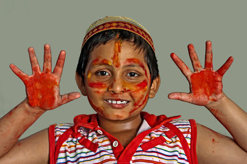 Young boy playing Holi, smiling with colors on face and hands, w