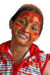 Young boy playing Holi, smiling with colors on face with cap