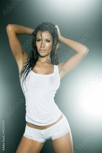 Wet woman wearing white transparent tank top and panties