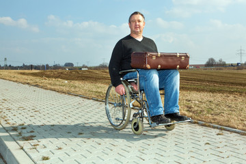 Man with suitcase wheelchair and walk on the road