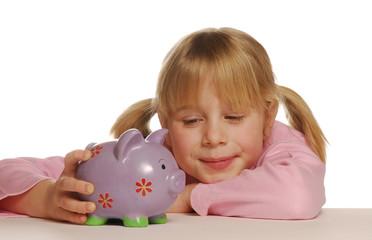 Pequeña niña sosteniendo un cerdito de ahorros.