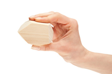 Human hand holding wooden block