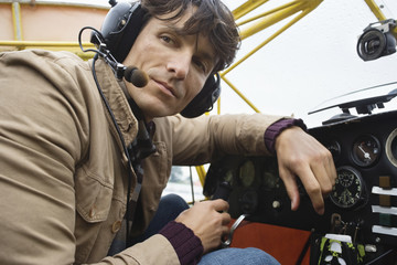 Young man sitting in airplane, portrait