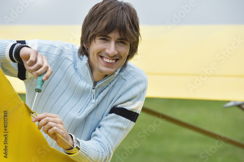 Young man screwing hook in airplane, smiling, portrait