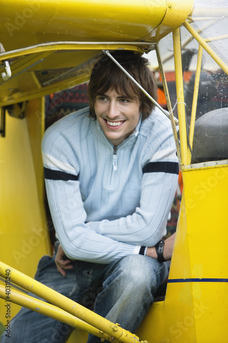 Young man sitting in airplane, smiling