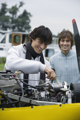 Young man screwing in airplane engine, smiling