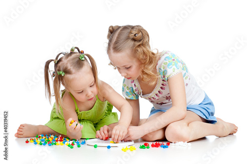 elder sister training young one to collect mosaic toy over white
