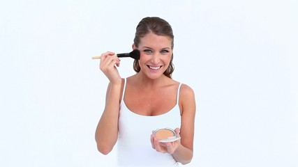 Laughing woman applying blush on her face