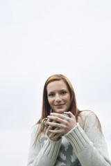 Young woman holding mug, smiling