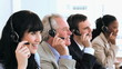 Joyful call centre agents sitting while wearing headsets