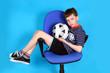 Постер, плакат: мальчик футболист отдыхает на офисном стуле