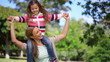 Woman turning while carrying her daughter on the shoulders
