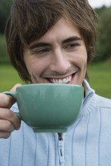 Young man holding mug, smiling