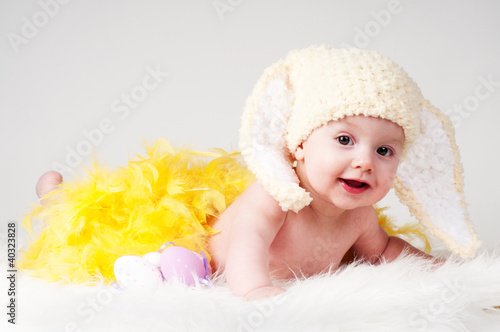 baby girl with yellow feather and Easter bunny ears