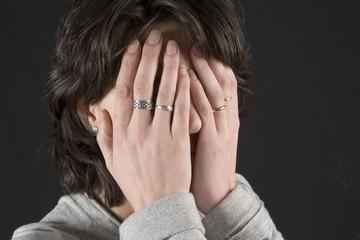 Mujer joven tapándose la cara con las manos.