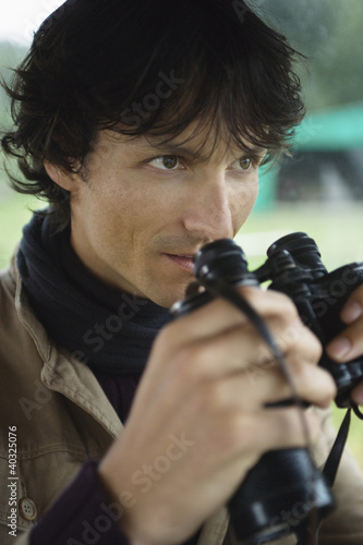 Young man holding binoculars, close-up