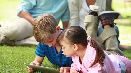Smiling siblings using an ebook while lying