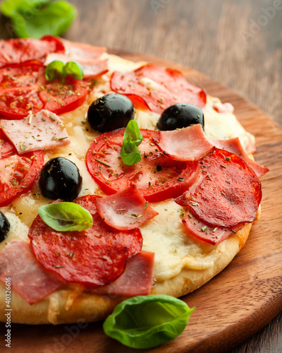 Pizza with salami, ham and tomatoes