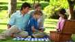 Happy family sitting on a blanket during a picnic