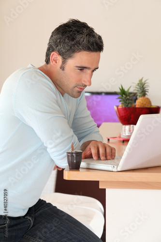 Man at home connected on internet with laptop