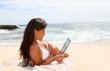Beautiful woman in bikini using tablet on the beach