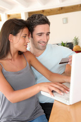 Couple at home doing online shopping with laptop