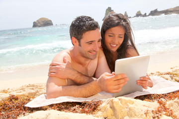 Couple at the beach using electronic tablet