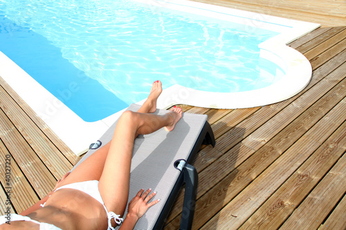 Closeup on legs of woman relaxing in deck chair by pool