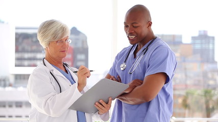 Serious mature doctor talking with a nurse